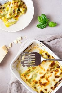 Homemade basil pesto is spread over fresh cannelloni pasta recipe and baked in a luscious cheesy provolone bechamel sauce and topped with mozzarella cheese, comfort food heaven! Insidetherustickitchen.com