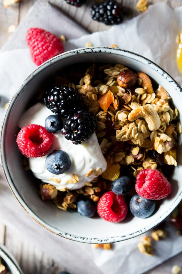 A close up of healthy granola in a blue bowl topped with yogurt and berries