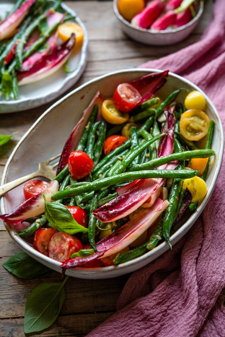 A side shot of a green bean salad in a large serving bowl