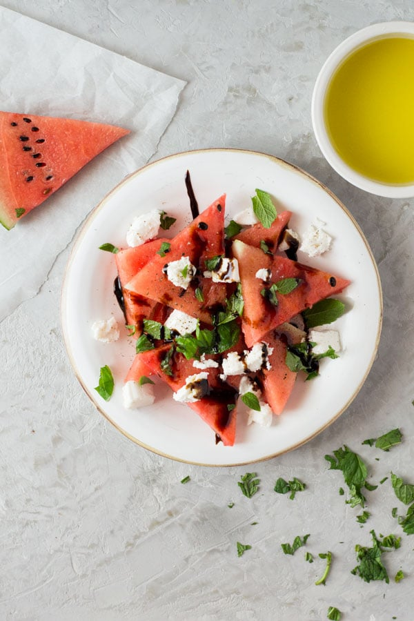 A delicious light watermelon basil salad with mint, goats and balsamic glaze. Refreshing and healthy salad recipe insidetherustickitchen