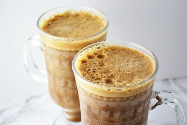 Tow glasses of banana milk coffee on a white surface