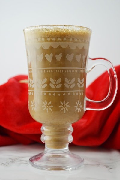 Banana milk coffee in a glass mug on a white surface