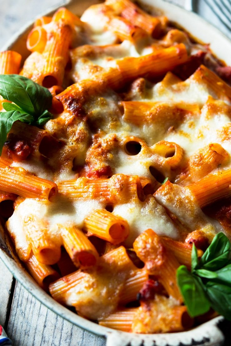 a close up shot of a sausage pasta bake with melted mozzarella in a large dish