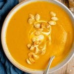 A close up image of pumpkin soup topped with pumpkin seeds