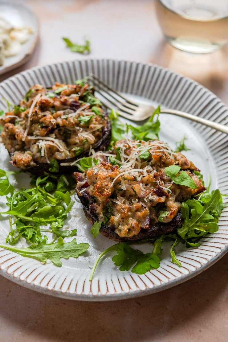A side shot of sausage stuffed mushrooms on a plate with arugula