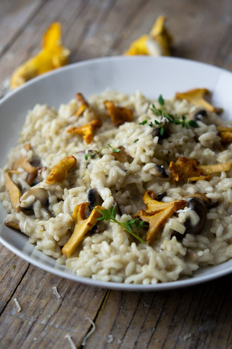 A side shot of creamy mushroom risotto in a white marble bowl