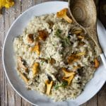 Creamy mushroom risotto in a bowl topped with extra mushrooms