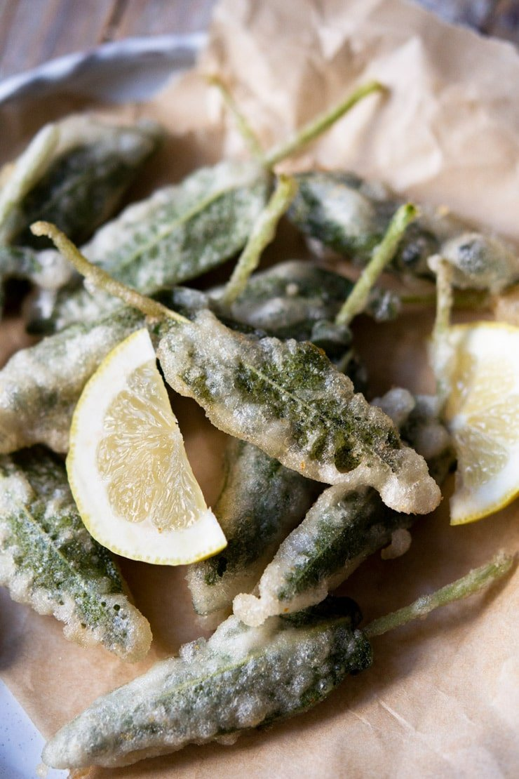 A close up of fried sage leaves in a plate with lemon wedges
