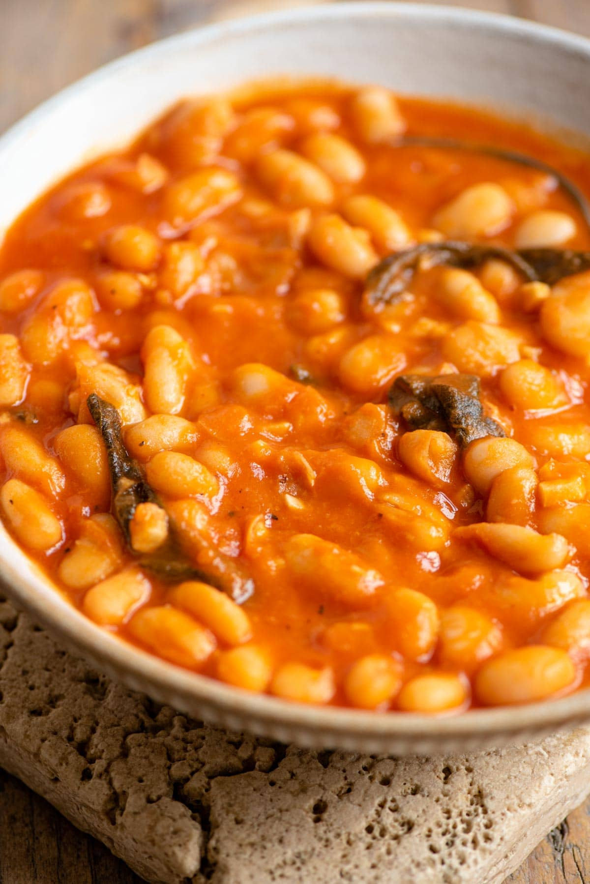 A close up of a bowl of beans in tomato sauce with sage leaves