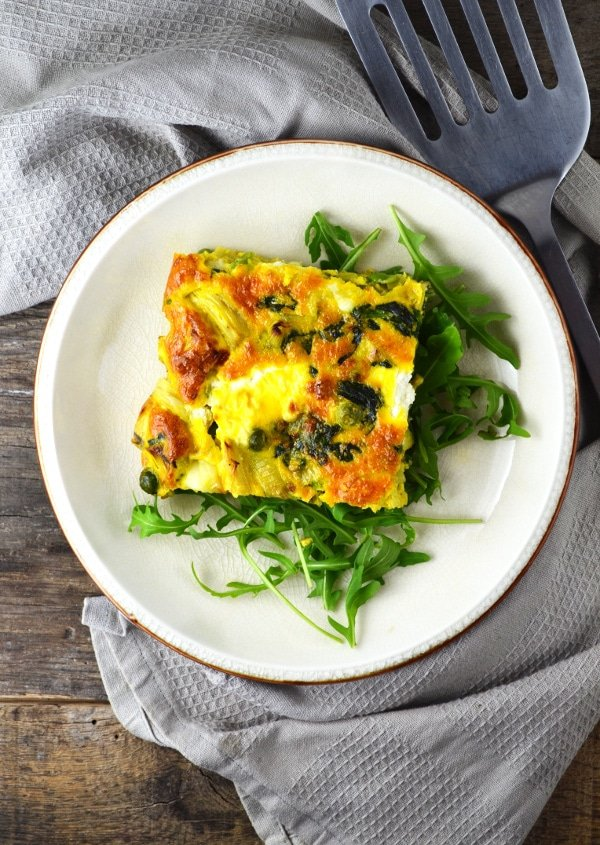 This Artichoke and Spinach Frittata is perfect for a light lunch this Spring with peas, leek and goats cheese it is packed full of flavour! www.insidetherustickitchen.com