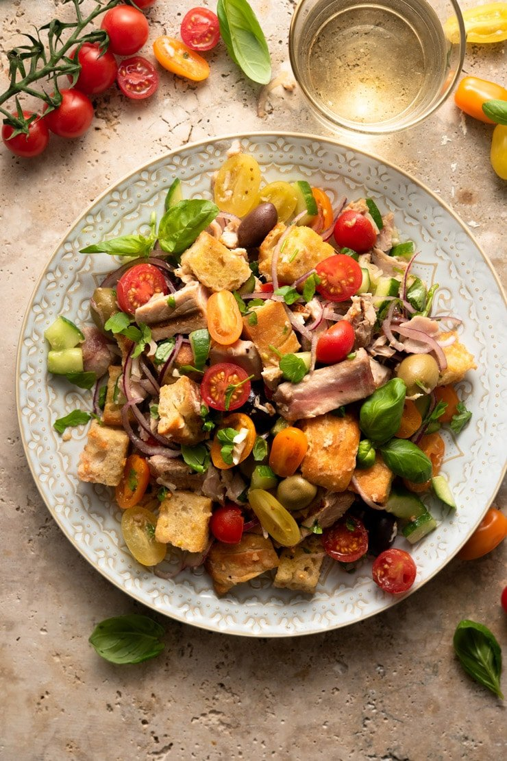 An overhead shot of a tuna panzanella salad on a large plate with tomatoes and basil scattered around