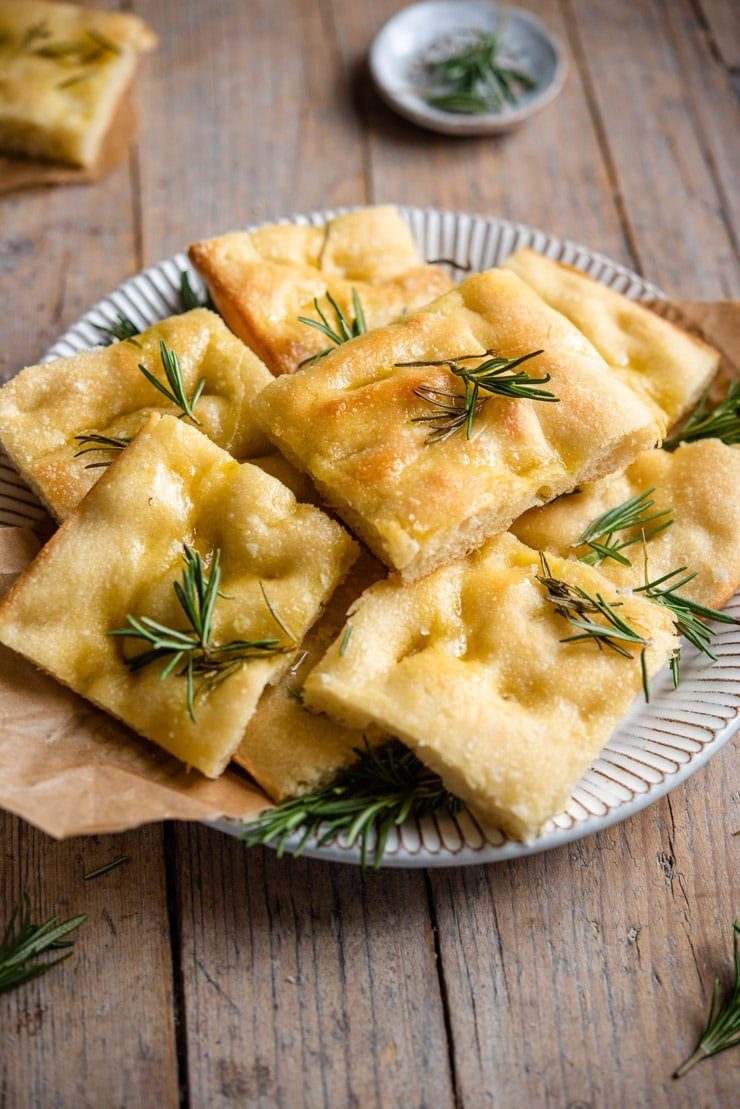 A side shot of rosemary focaccia cut into squares on a rustic plate