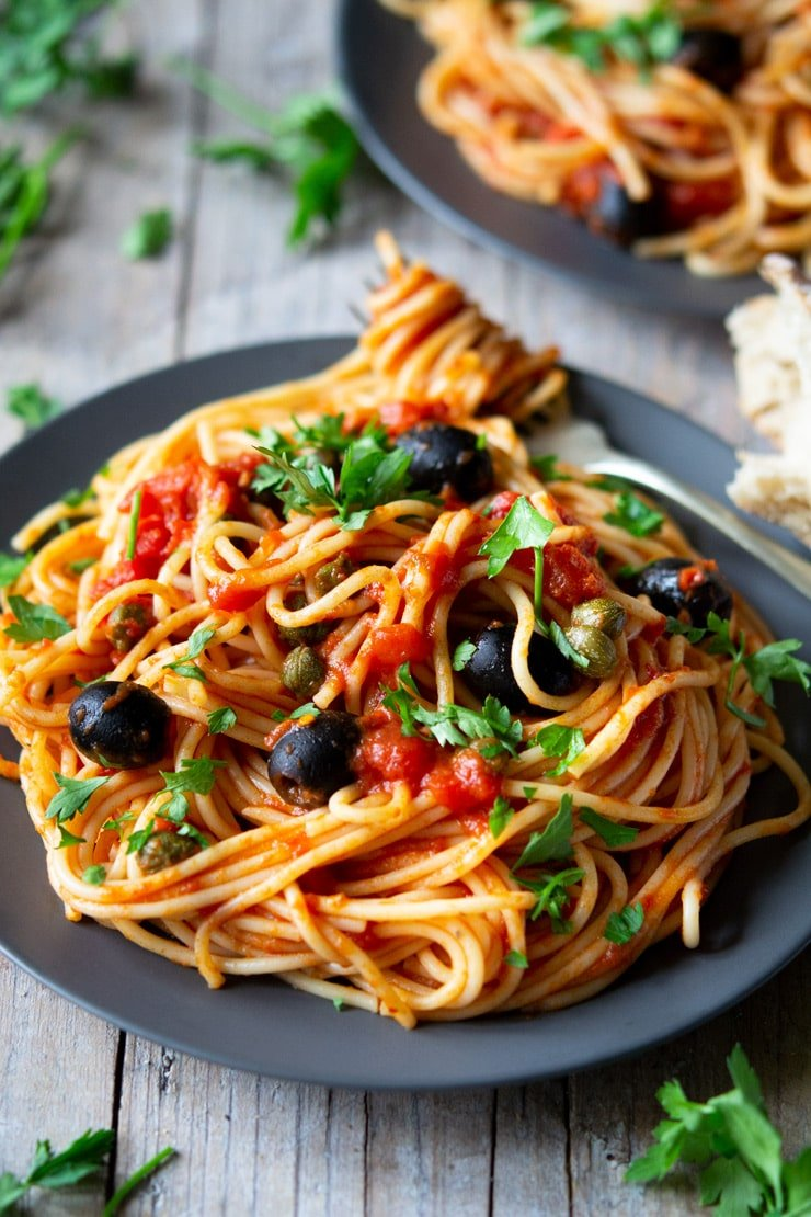 A close up of spaghetti on a plate with puttanesca sauce sitting on a wooden surface