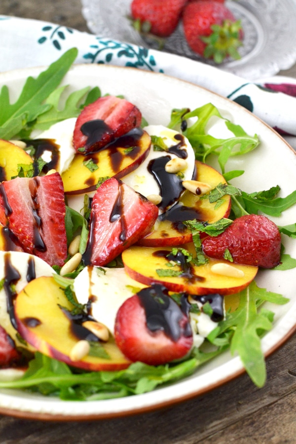 Roasted strawberries, sweet peaches, and delicious mozzarella cheese are sprinkled with mint, toasted pine nuts, and balsamic glaze. It's fresh, light and perfect for summer. insidetherustickitchen.com