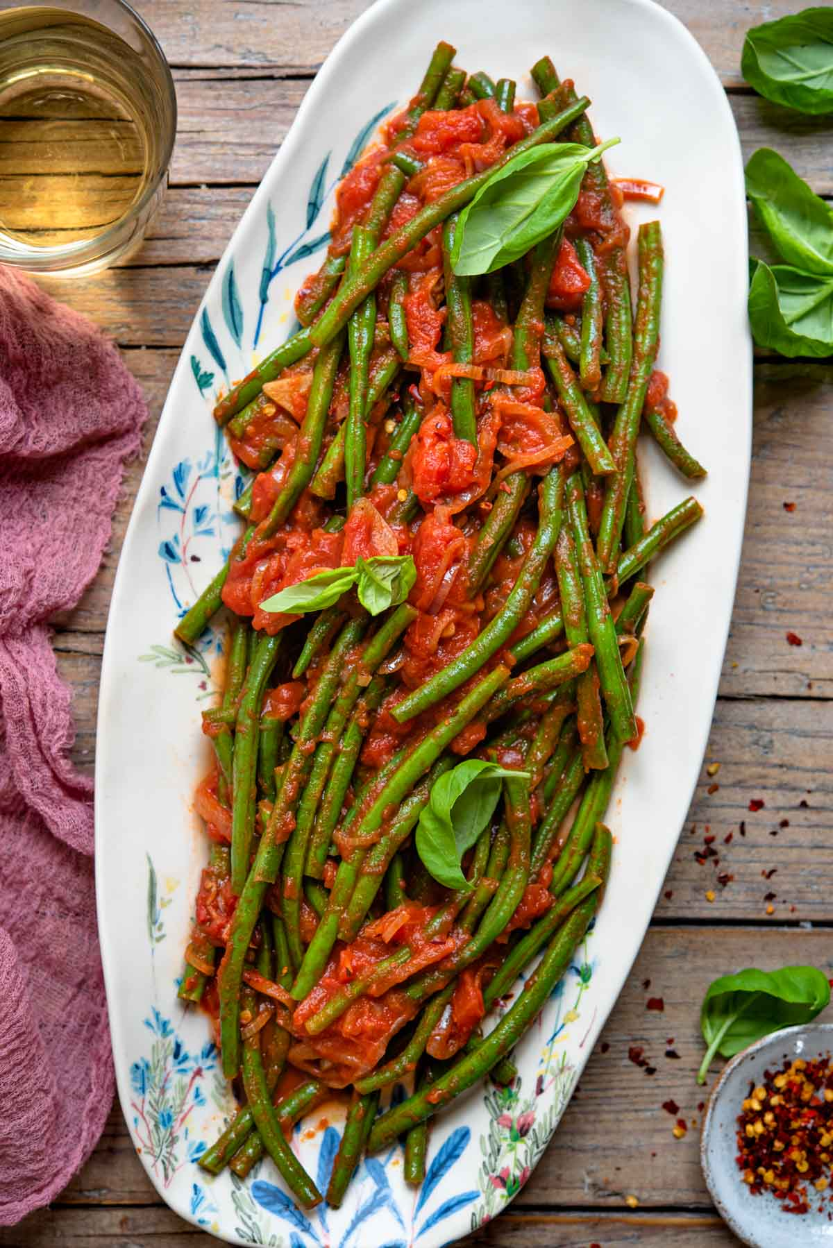 An overhead shot of Italian green beans tossed in a tomato sauce on an oval plate