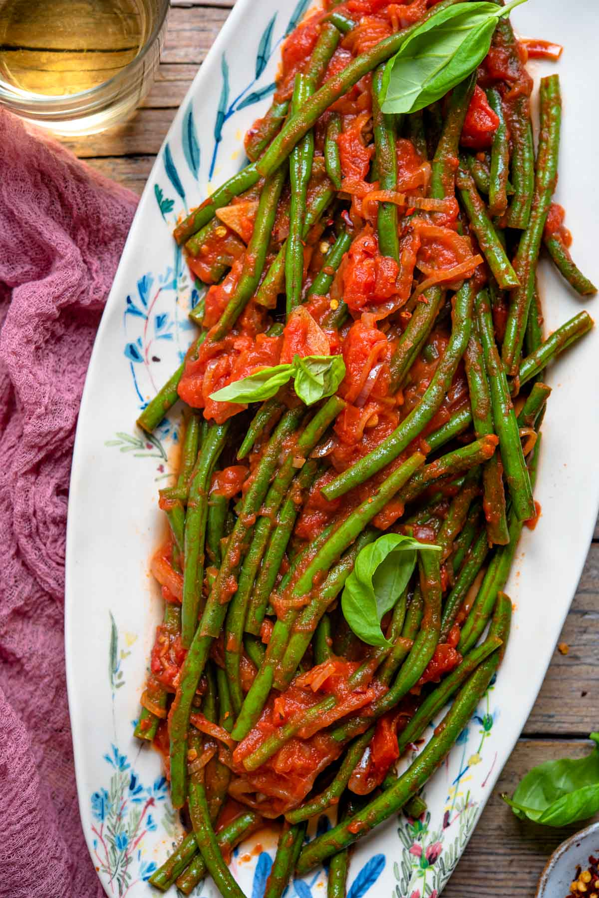 A close up of Italian green beans in tomato sauce on a oval plate
