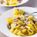 A delicious speck and mushroom pappardelle pasta made with a simple and incredibly delicious creamy sauce. www.insidetherustickitchen.com