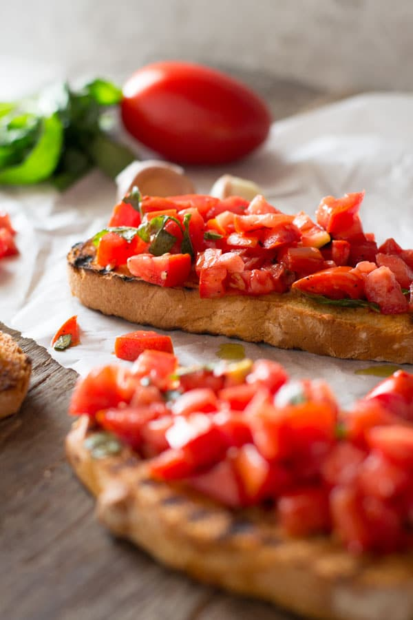 A close up of chopped fresh tomatoes on toasted garlic bread sitting on a wooden board