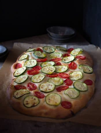 Delicious zucchini tomato focaccia. A simple Italian snack or appetizer with a crispy crust and soft, light and fluffy middle. Authentic Italian recipes and traditional Italian recipes at Inside the rustic kitchen.