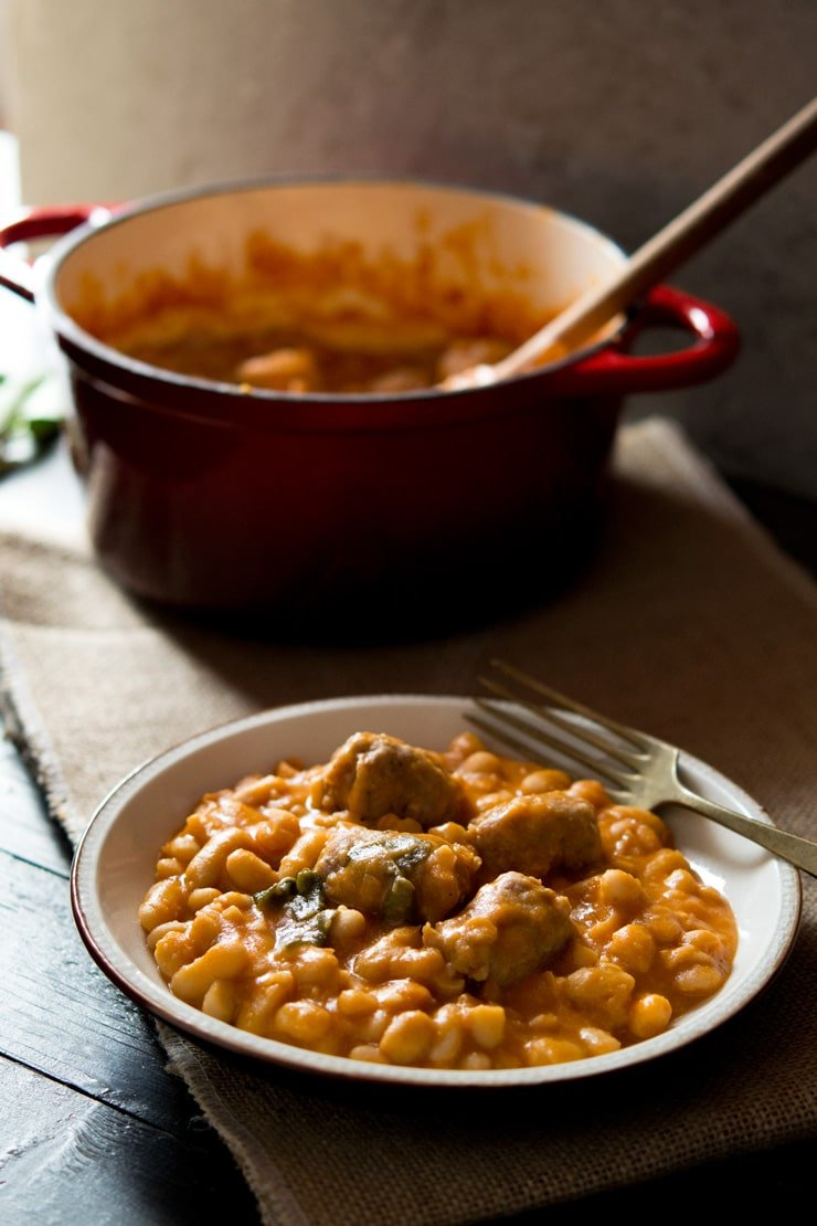 A close up of Tuscan bean stew with sausages on a plate with a fork, pot in the background.