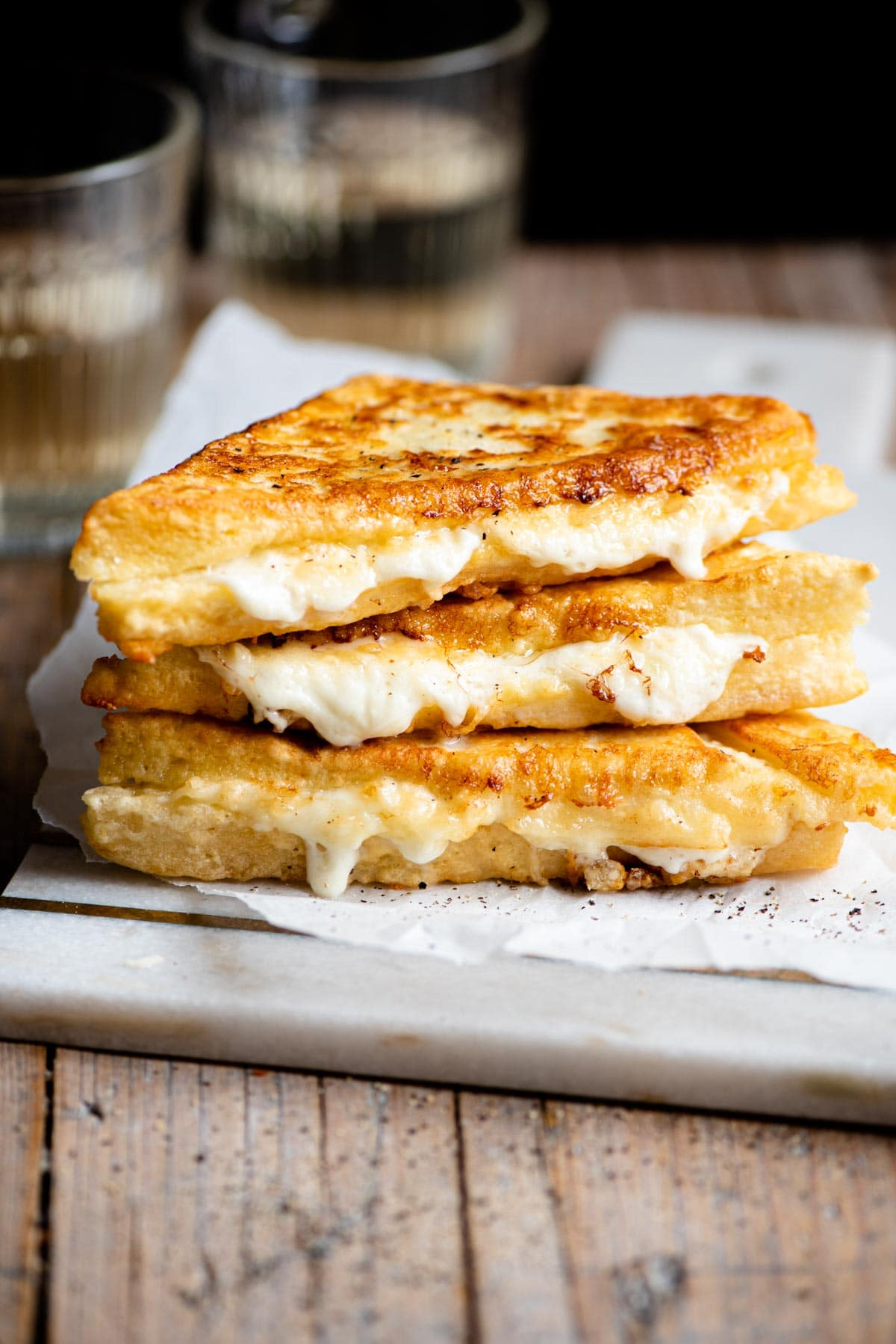 Three fried mozzarella sandwiches stacked on top of each other