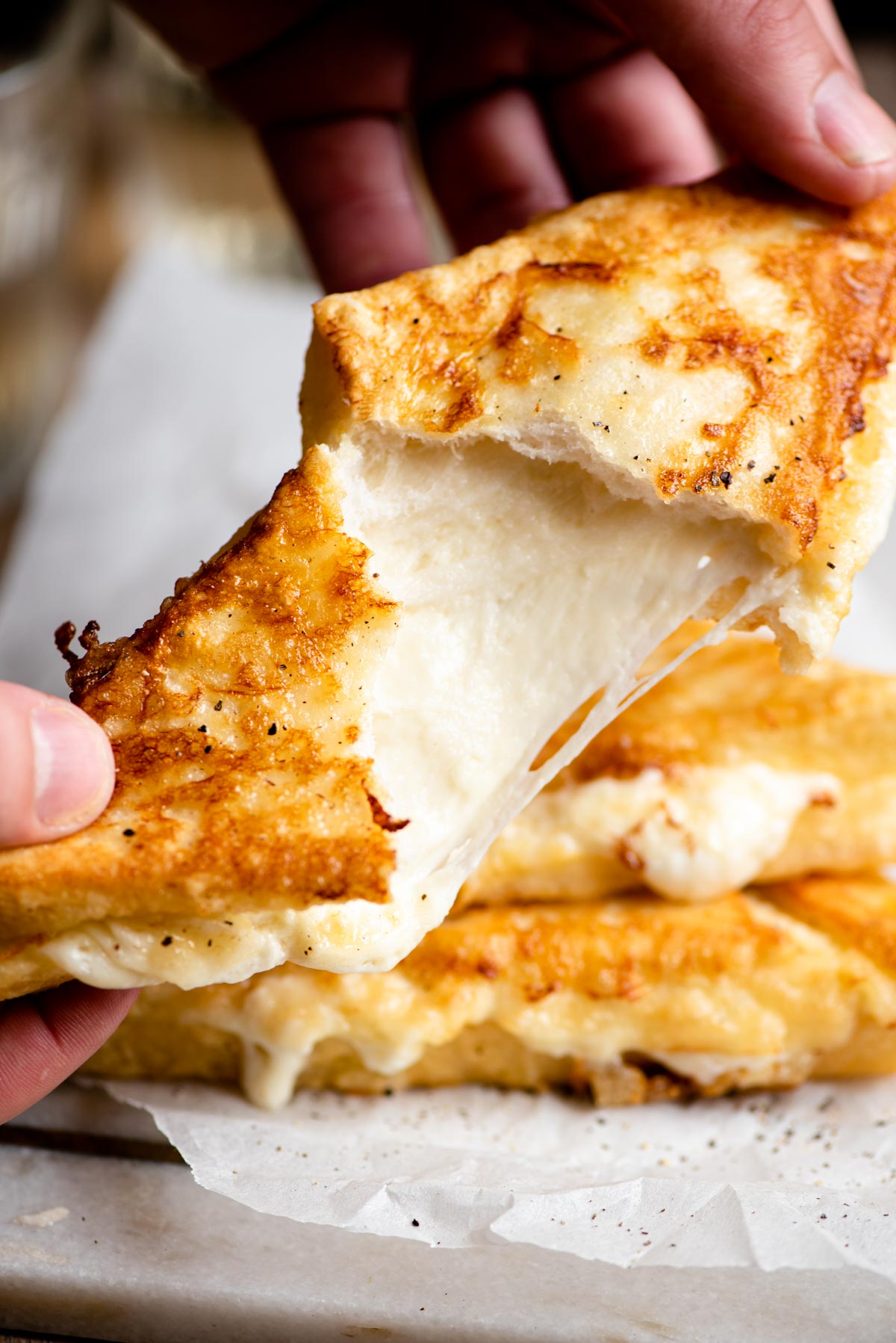 A close up of a fried mozzarella sandwich broken open with cheese oozing and stretching