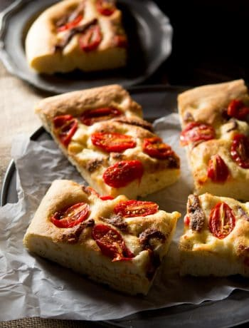 Cherry tomato focaccia with anchovies cut into slices sitting on a rustic plate