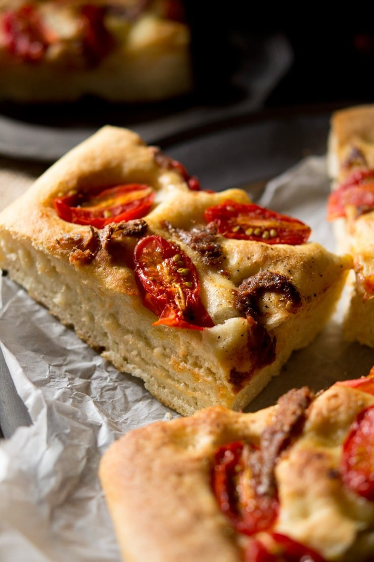 Close up of cherry tomato focaccia with anchovies cut into a slice