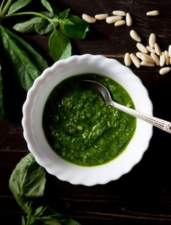 Recipe for how to make basil pesto, pesto in a bowl with basil and pine nuts