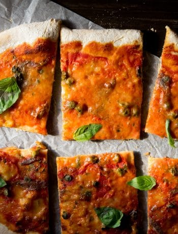 anchovy pizza a.k.a pizza napoli cut in slices on baking parchment