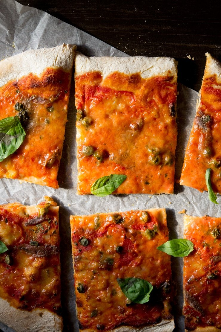 An overhead close up of anchovy pizza with capers cut into slices