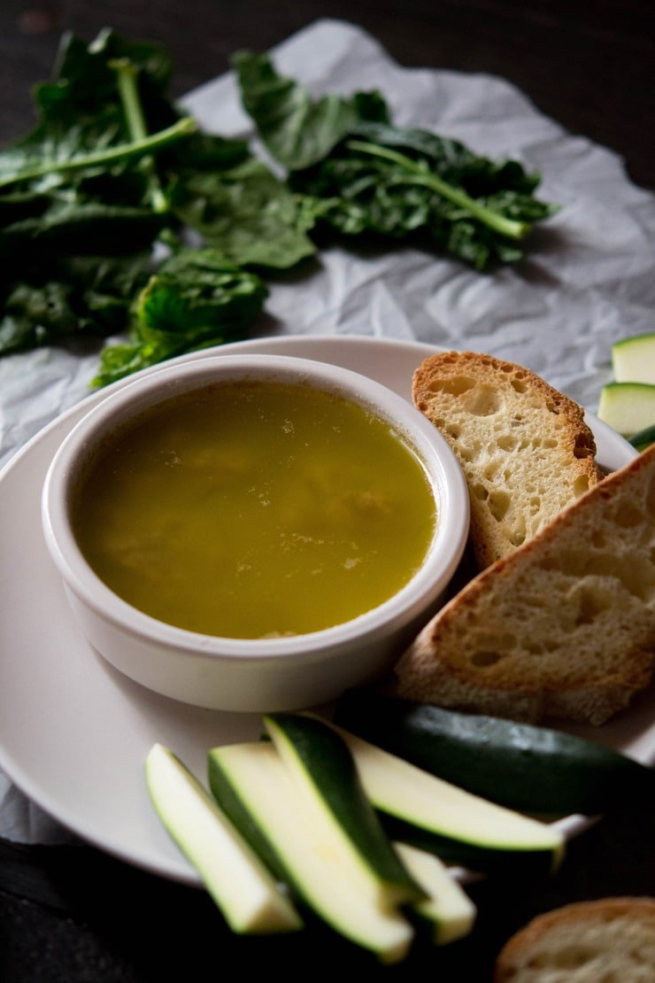 A close up shot of bagna cauda in a ramekin with sliced ciabatta - bagna cauda recipe