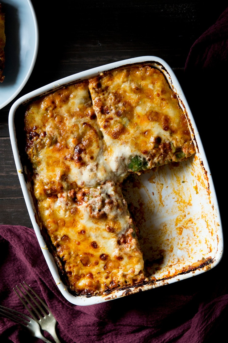 an overhead shot of beef lasagne with one slice taken out of the dish