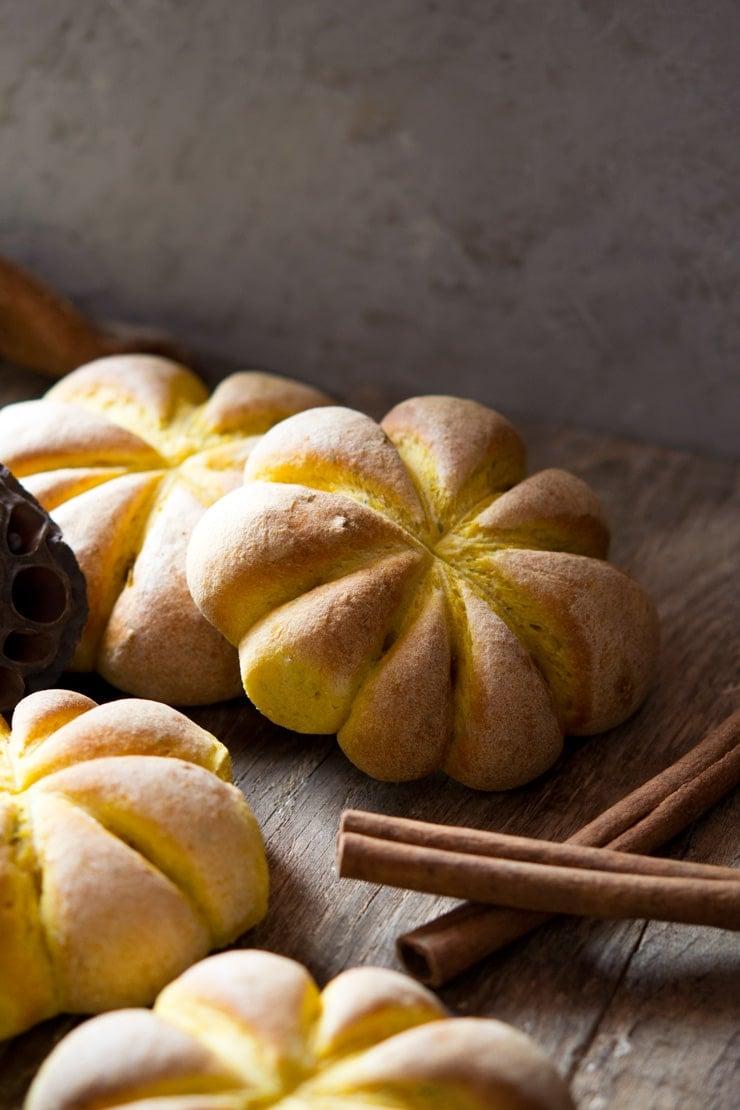 Pumpkin bread rolls sitting on a wooden surface (the rolls are pumpkin shaped)