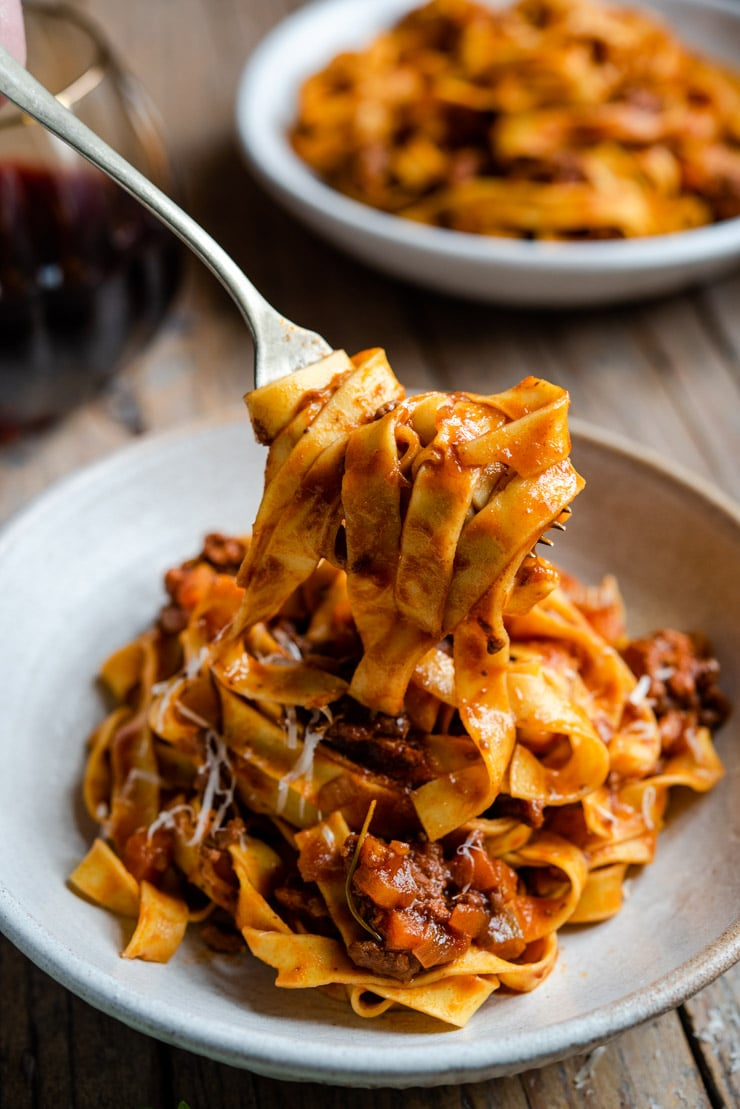 A close up of Italian beef ragu and pasta on a fork