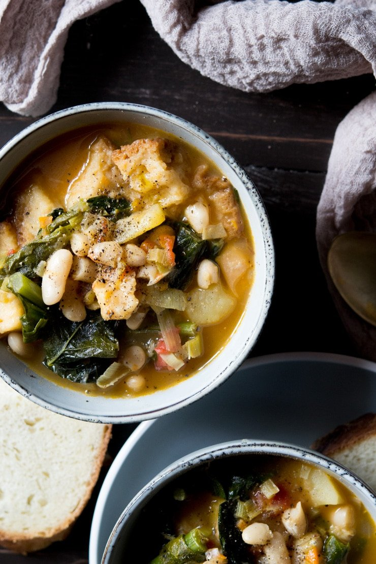 Overhead shot of ribollita Tuscan vegetable stew with bread in background