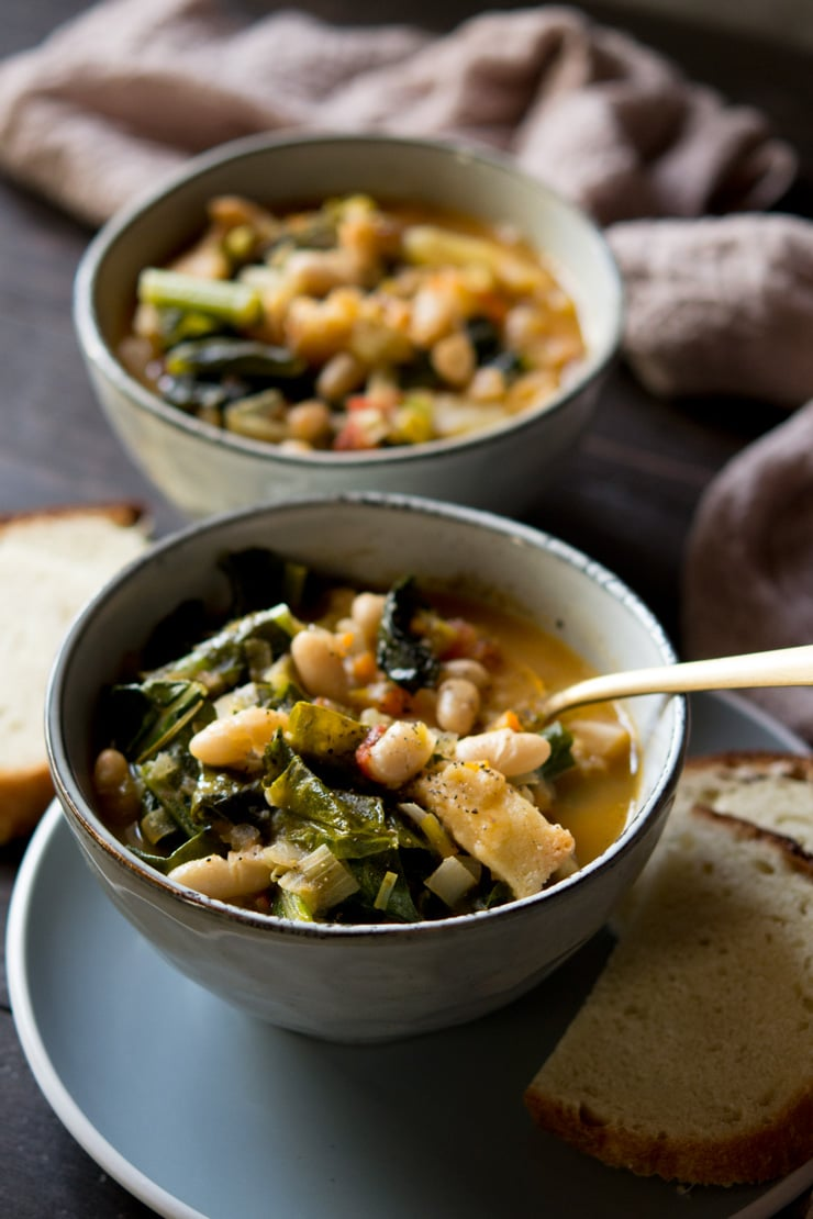 Tuscan vegetable soup in a bowl with bread in background