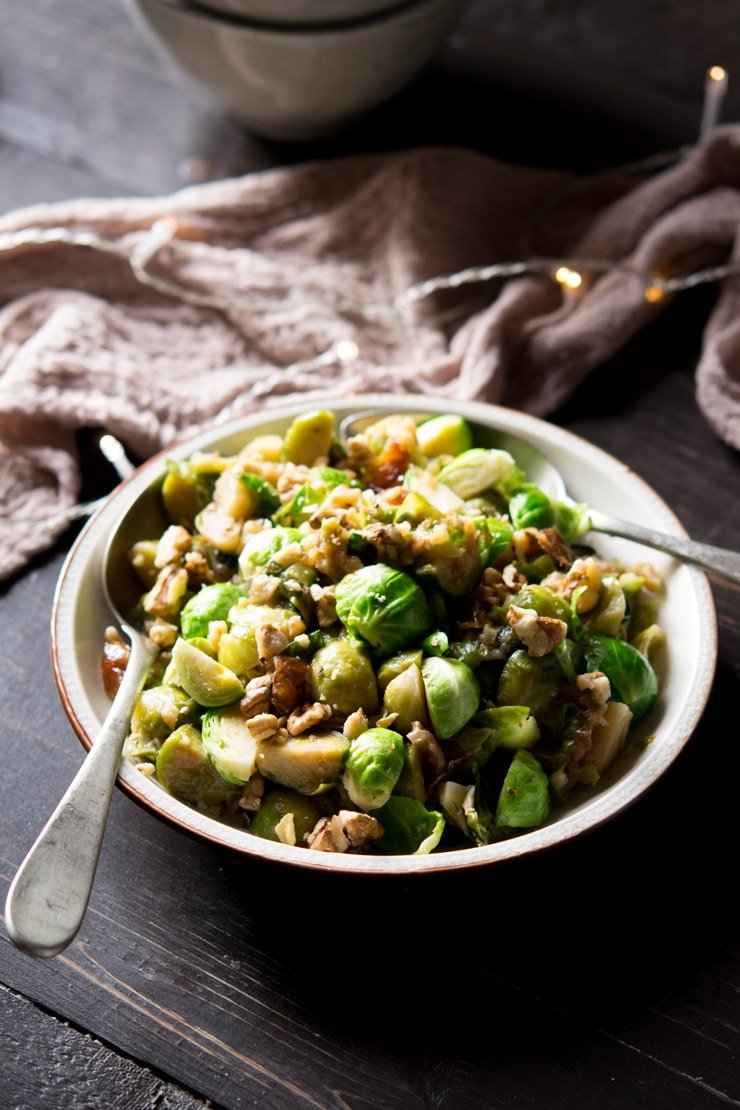 sauteed brussels sprouts with dates and walnuts on a serving plate with spoons