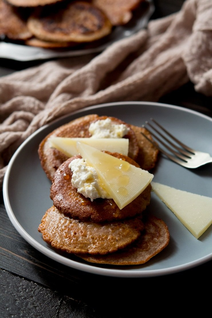 chestnut fritters on a plate topped with ricotta and pecorino cheese