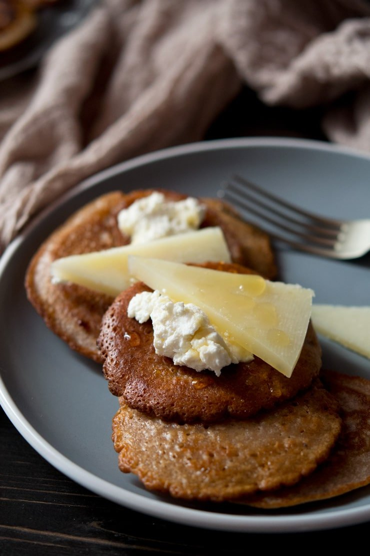 a close up of chestnut fritters topped with pecorino cheese, ricotta and honey
