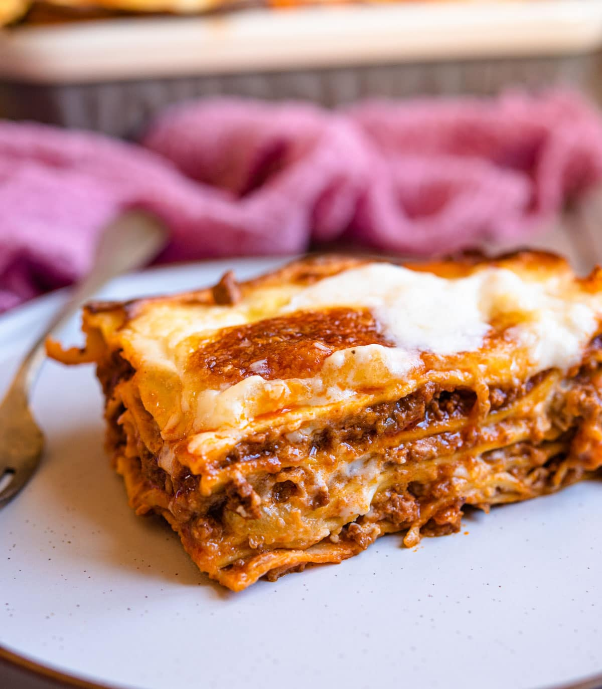 A close up of a slice of lasagne al forno on a plate
