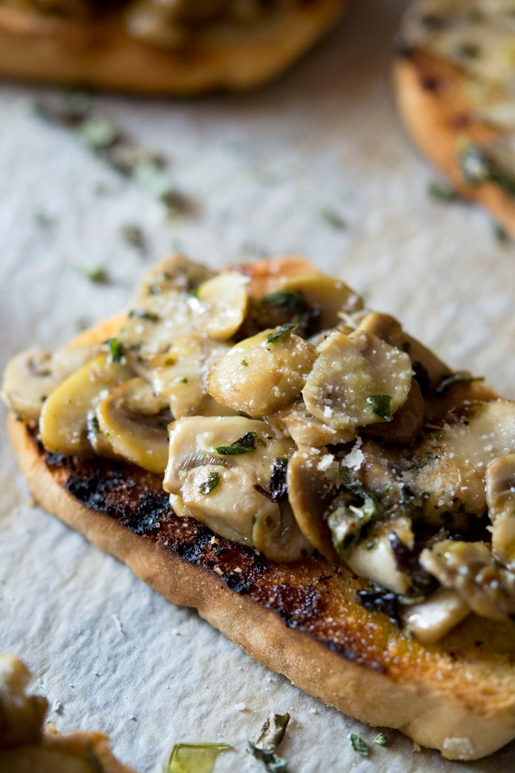 A close up of mushroom toasts with oregano and parmesan