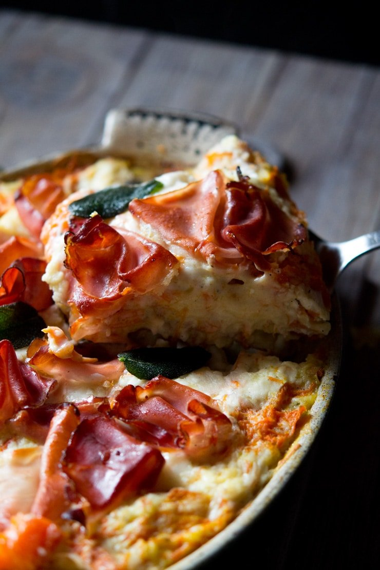 A close up shot of a slice of butternut squash lasagna topped with prosciutto