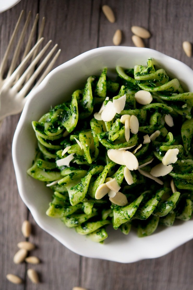 A close up of pesto pasta sauce with fusilli pasta in a white bowl