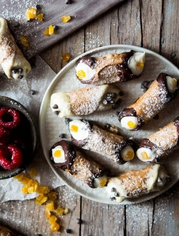 Mini cannoli on a plate with candied orange