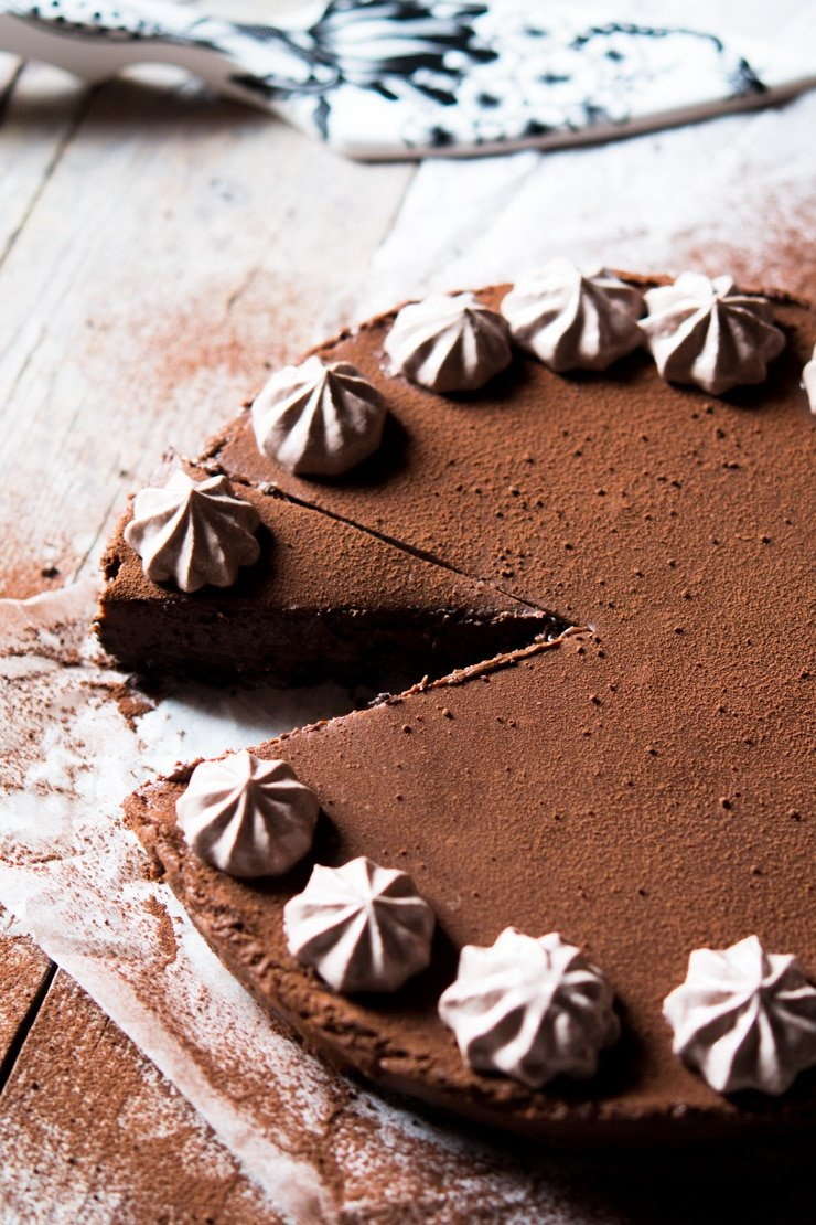 a slice of no bake chocolate cheesecake cut out and sitting on a wooden surface