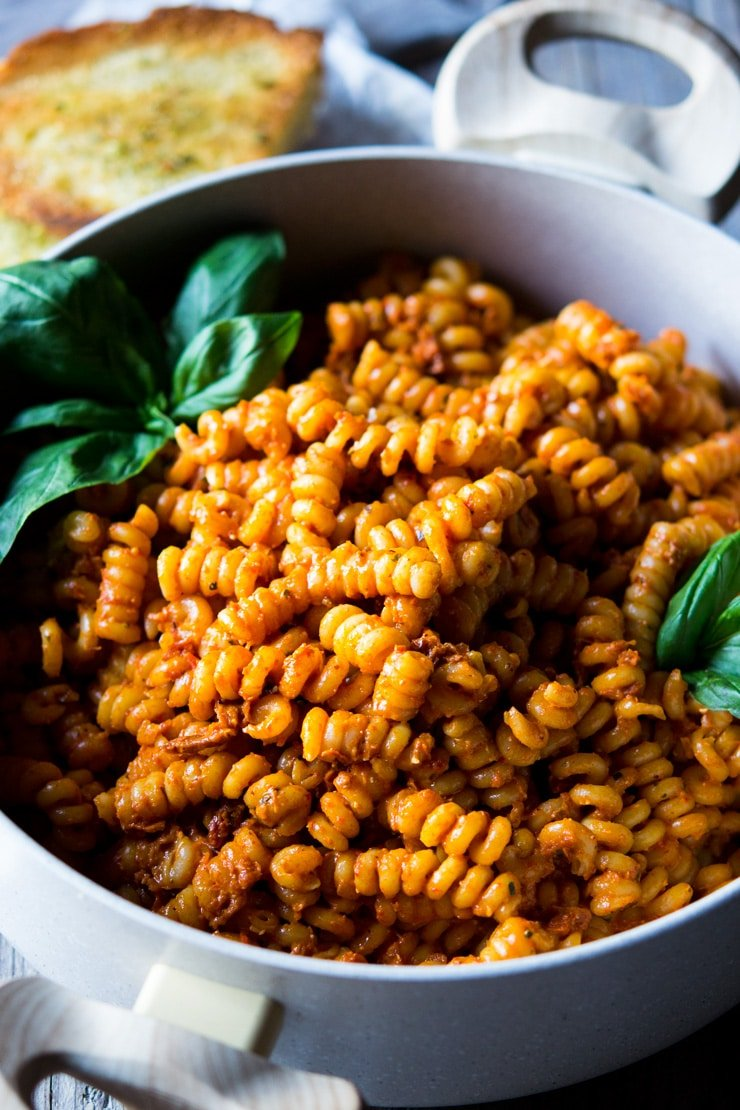 a close up of sun dried tomato pasta and basil