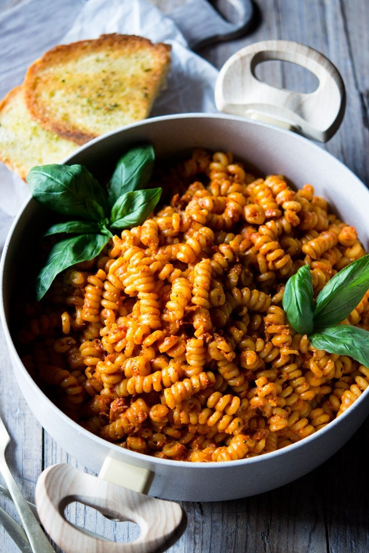 sun dried tomato pasta in a pot with basil and garlic bread