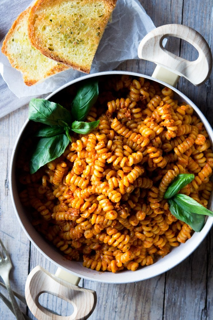 An overhead shot of sun dried tomato pasta in a large pot with basil
