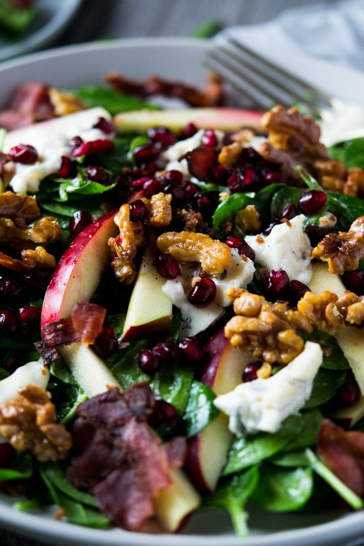 a close of a winter salad made with apple, spinach, pomegranate and gorgonzola